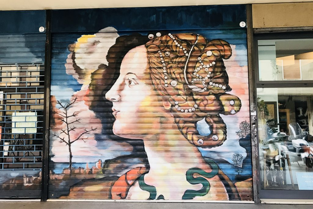 street art painted on shop shutters in Via Del Pratello Bologna Italy, lady head with beads in hair