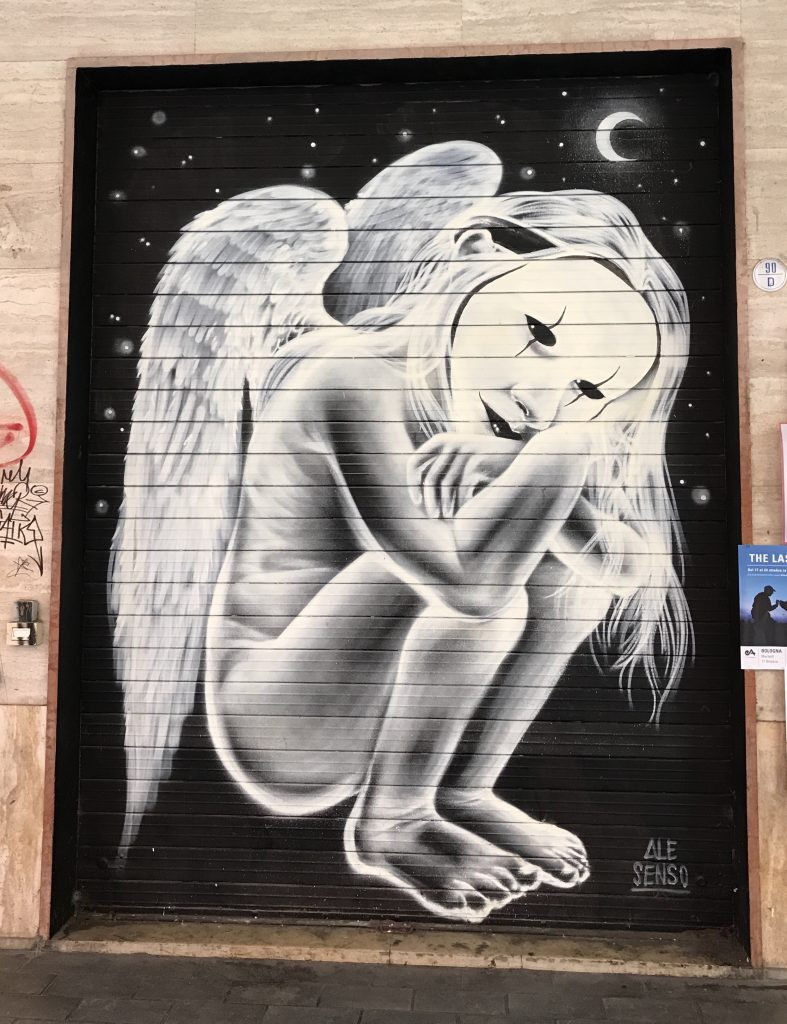 street art painted on shop shutters in Via Del Pratello Bologna Italy, angel