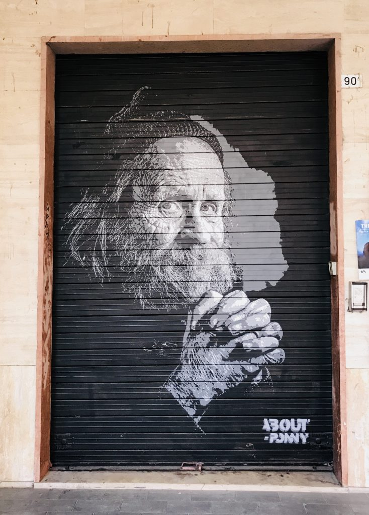 street art painted on shop shutters in Via Del Pratello Bologna Italy, old man with beard and beanie