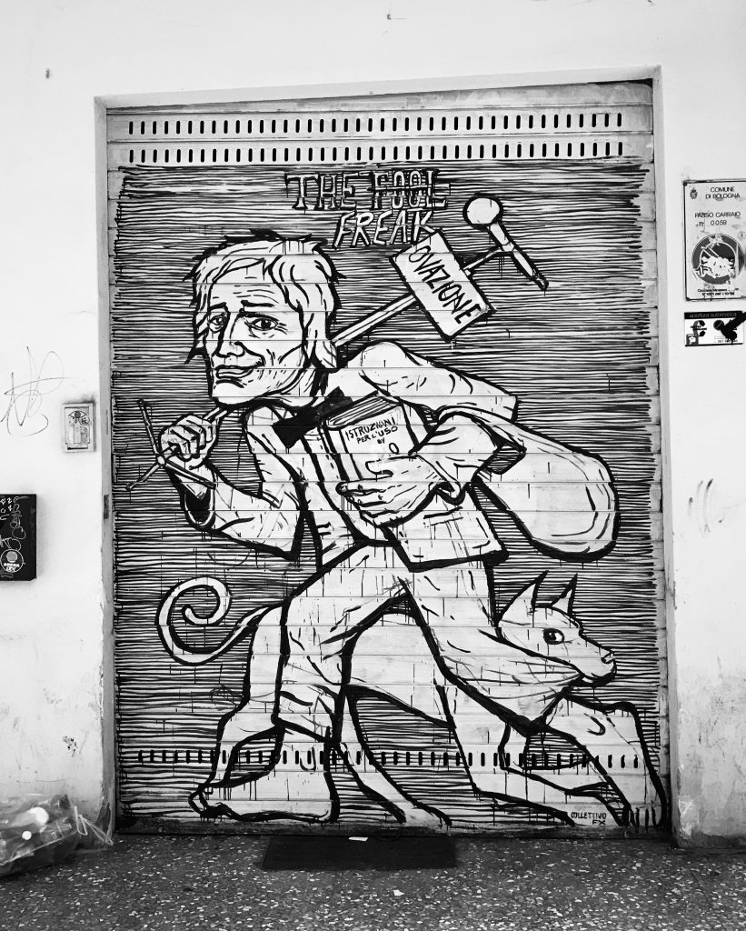 street art painted on shop shutters in Via Del Pratello Bologna Italy, the fool freak, man with a dog