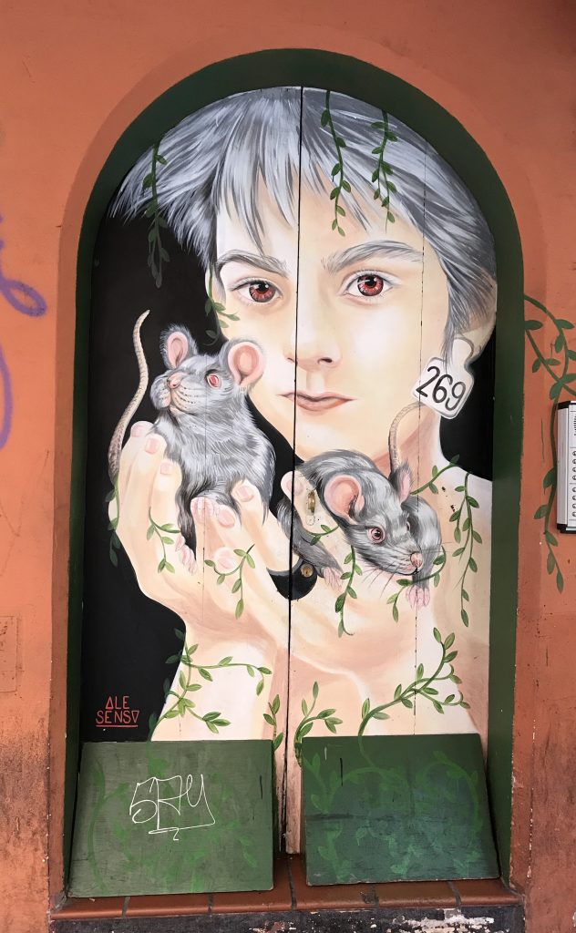 street art painted on shop shutters in Via Del Pratello Bologna Italy, last holding 2 mice
