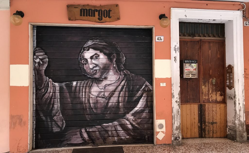 street art painted on shop shutters in Via Del Pratello Bologna Italy, old lady looking through a window