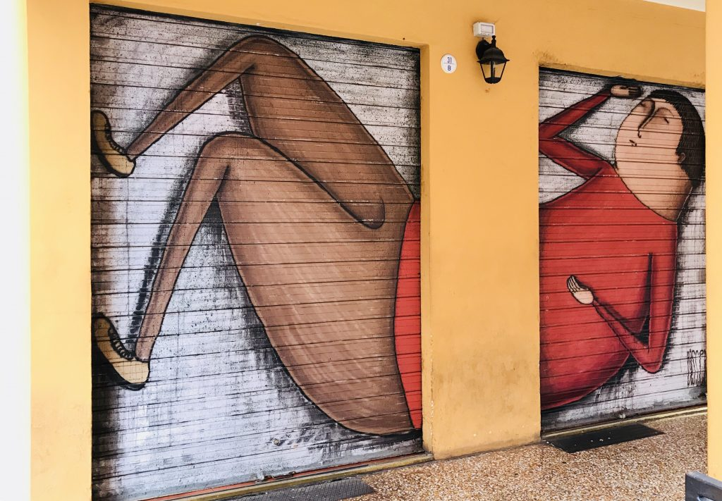 street art painted on shop shutters in Via Del Pratello Bologna Italy, man lying down
